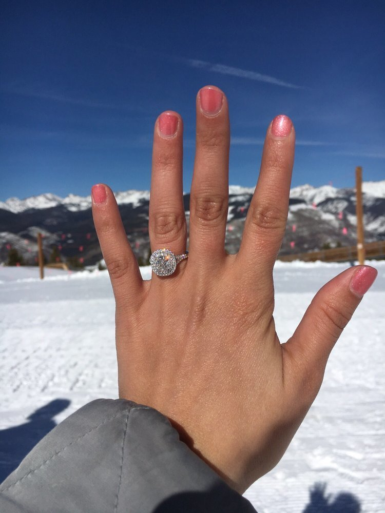 A cushion cut double halo engagement ring on a hand in front of a snowy backdrop.